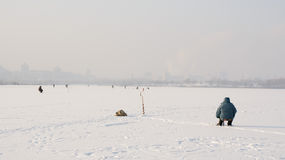 Frozen lake in town with fishermen in the background houses, ice fishing. Stock Photos