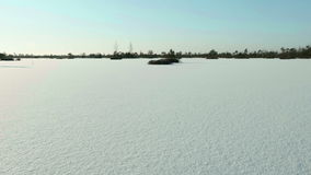 Frozen lake under the snow. Clean and frosty daytime. Smooth dolly shot. Frozen lake under the snow in the national wildlife reserve. Clean and frosty daytime stock video footage