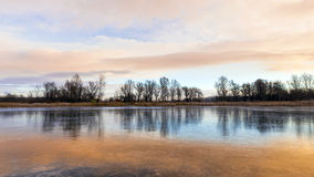 Frozen lake in winter beautiful colors. Frozen lake in Europe in Hungary, reflecting the ice beautiful colorful clouds Stock Photo