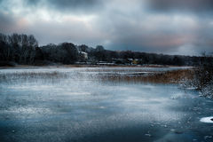 Frozen lake. In winter. Mansion in background Stock Photo
