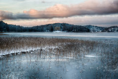 Frozen lake. In winter. Mansion and village in background stock photography