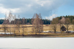 Frozen lake at winter, small cabin cottage house, forest hill background Royalty Free Stock Image