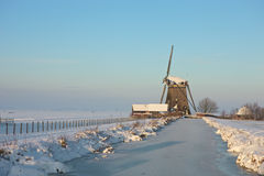 Frozen landcape with windmill. A sunny winter day in Dutch landscape with windmill Royalty Free Stock Images