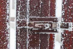 Frozen latch on brown wood fence frozen due to extreme cold Stock Photography