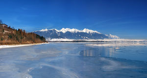 Frozen Liptovska Mara and Western Tatras. This winter view shows the frozen Liptovska Mara lake with the Rohace mountains and the peak of Krivan in the distance stock image
