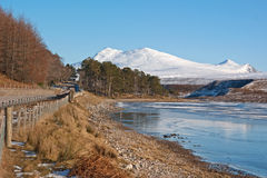 Frozen loch and snow clad mountain Stock Photo