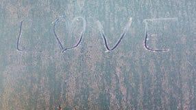 Frozen love on car window with heart shape on frosty windscreen Stock Photos