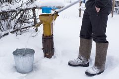 A frozen man in felt boots pours clean drinking water into a bucket using a water pump, against the backdrop of a snow-covered. Garden, on a cold winter evening royalty free stock image