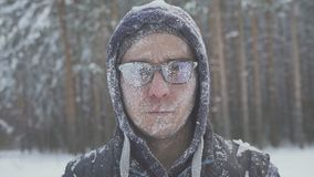 A frozen man with glasses in the snow looks at the camera in the winter forest after a snow storm. Immunity and cold Royalty Free Stock Photo