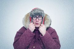 Frozen man in glasses and winter clothes warming ears, cold, snow, blizzard Royalty Free Stock Photos