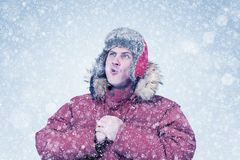Frozen man in red winter clothes lets the steam out of his mouth, cold, snow, blizzard stock photography