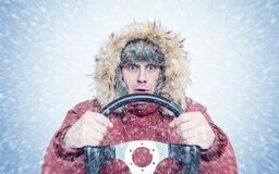Frozen man in red winter clothes with a steering wheel, snow blizzard. Concept car driver royalty free stock images