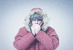 Frozen man in red winter clothes warming hands, cold, snow, frost, blizzard royalty free stock photos