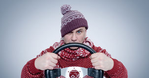 Frozen Man in sweater and hat with a steering wheel. Concept car driver Royalty Free Stock Photo