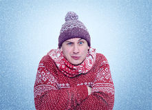 Frozen man in sweater, scarf and hat warming hands, cold, snow, blizzard Stock Photos