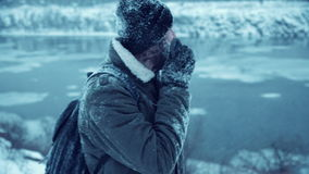 Frozen man using radio equipment and talking. Man with ice glazed beard on the mountain browsing for a signal to find a way and talk using radio comunication stock footage
