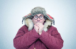 Frozen man in winter clothes and glasses warming hands, cold, snow, blizzard Stock Photo