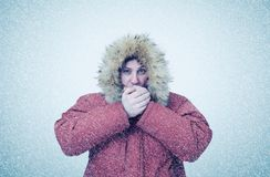 Frozen man in winter clothes warming hands, cold, snow, blizzard Royalty Free Stock Image