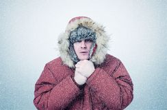 Frozen man in winter clothes warming hands, cold, snow, blizzard.  Royalty Free Stock Photo
