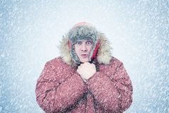 Frozen man in winter clothes warming hands, cold, snow, blizzard Stock Photos