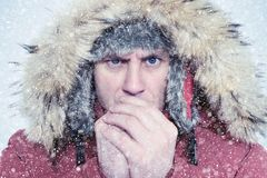 Frozen man in winter clothes warming hands, cold, snow, blizzard.  Royalty Free Stock Image