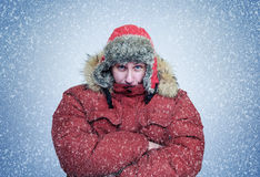 Frozen man in winter clothes warming hands, cold, snow, blizzard royalty free stock images