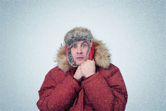 Frozen man in winter clothes warming hands, cold, snow, blizzard.  Royalty Free Stock Images