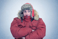 Frozen man in winter clothes warming hands, cold, snow, blizzard Stock Image