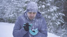 Frozen man in the winter forest uses the phone. Frozen man covered with snow in the winter forest uses the phone stock images