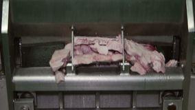 Frozen meat cutting machine operating in a meat processing factory stock footage