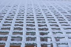 Frozen metal iron net chequer covered with frost in winter. Frozen metal iron net chequer grid covered with frost in winter close-up stock photos
