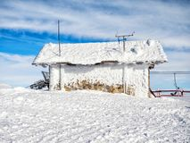 Frozen meteo station. Frozen small meteorological station at the top of the mountain Helmos in Kalavrita ski resort  in a sunny day Royalty Free Stock Photos
