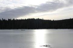 Frozen Milovy lake, Vysocina area, Czech Republic. Beautiful frozen lake surrounded by woods on a cold winter day stock image