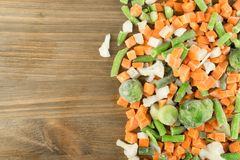 Frozen Mixed Vegetables. On Wooden Background. Raw Chopped Carrot, Cauliflower, Onion, Green Beans and Brussels Sprouts stock images