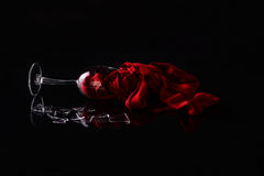 Frozen moment. Broken glass of wine with a red scarf symbolizing frozen wine, studio shot, still life royalty free stock image