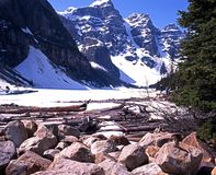 Frozen Moraine Lake, Canada. View across a frozen Moraine Lake towards the snow capped mountains during the Springtime with chipmunks on the rocks in the Stock Images