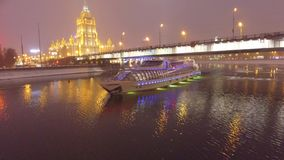 Frozen Moscow River cruise ship icebreaker Ukraine hotel at background. Night evening illumination Center of capital Russia. Unique aerial drone 4K footage. In stock footage