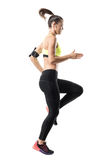 Frozen motion of fit female athletic runner doing high knees warm up exercise Stock Photo