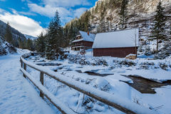 Frozen mountain river and wooden cottage in winter, Tatra Mountains Stock Photo