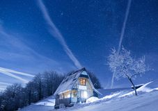 Frozen mountains cabin under a night sky filled with stars stock images