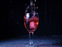 Ice falling on a glass with drink that spills and splashes. stock photo