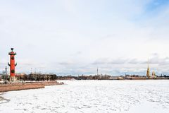 Frozen Neva river with Rostral Column and Fortress. View of frozen Neva river and Spit of Vasilyevsky Island with Rostral Column and Peter and Paul Fortress in Royalty Free Stock Images