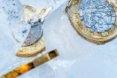 Frozen New British one pound sterling coin up close macro inside ice cubes.  Royalty Free Stock Photo