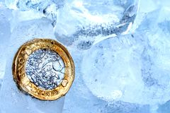 Frozen New British one pound sterling coin up close macro inside ice cubes.  Royalty Free Stock Photography