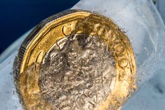 Frozen New British one pound sterling coin up close macro inside ice cubes.  Royalty Free Stock Photos