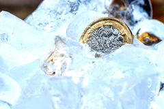 Frozen New British one pound sterling coin up close macro inside ice cubes.  Stock Image