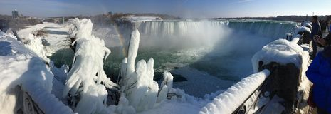 Frozen Niagara Falls. Landscape panorama of the frozen waterfalls in Ontario, Canada. Rainbow over the frozen waterfalls royalty free stock photo