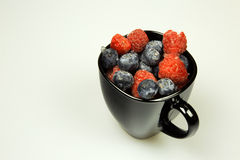 Frozen northern highbush blueberry and raspberries in black cup Stock Photography