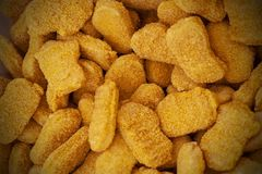 Frozen nuggets spread out evenly as a background. royalty free stock images