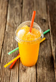 Frozen Orange Slushie in Plastic Cup with Straw. Close Up of Refreshing and Cool Bright Orange Slush Drink in Plastic Cup with Lid Served on Rustic Wooden Table royalty free stock photography